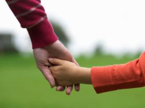a-woman-holding-hand-of-child